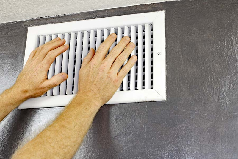 two hands on white wall vent