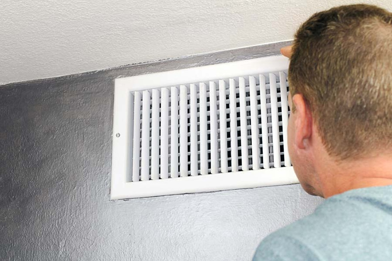 man in blue shirt looking at white air vent