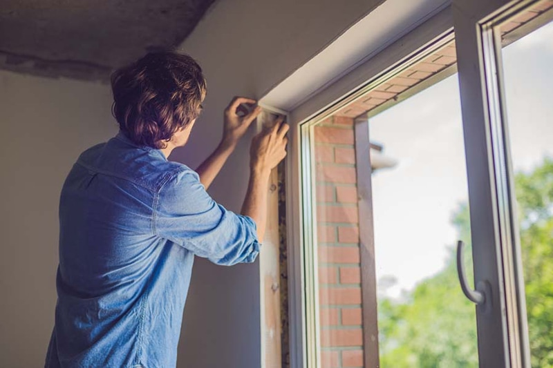 Man in a blue shirt does window installation