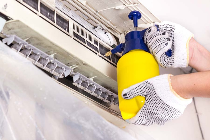 Technician spraying chemical water onto air conditioner coil to clean and disinfect