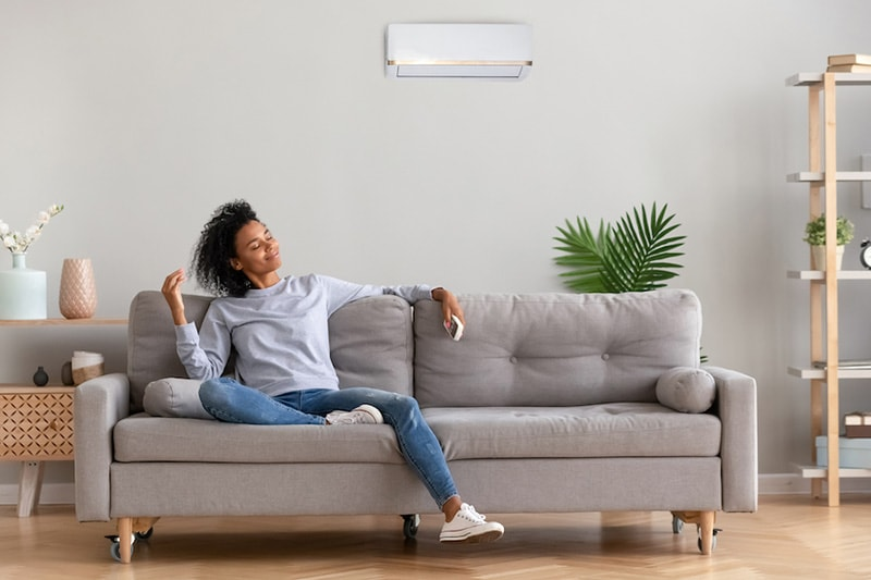 Young woman relaxing on a gray couch, What Accessories Can Help With My Indoor Air Quality? | HVAC Service
