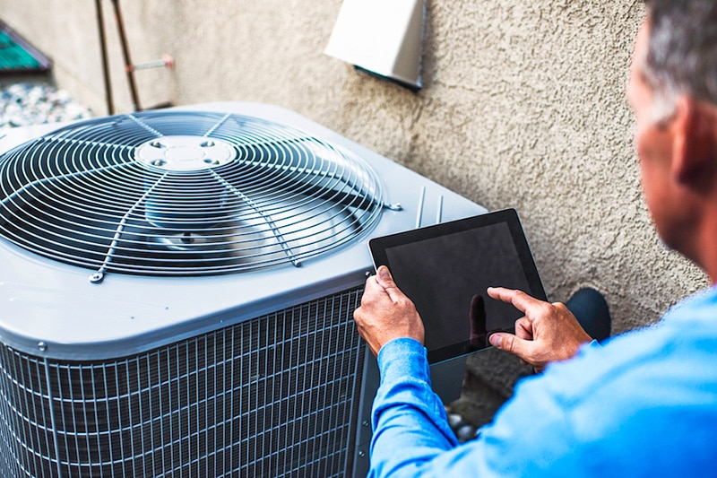 Maintenance engineer using digital tablet to inspect air conditioning unit, Fall HVAC Maintenance | All Seasons Heating & Air Conditioning | Asheville