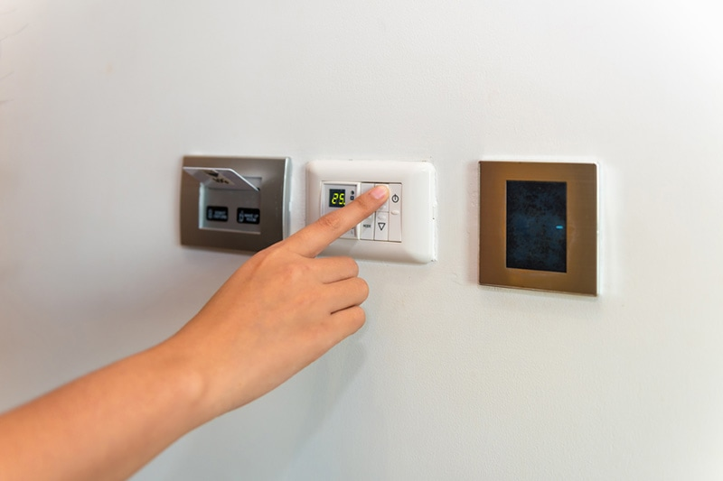 Hand adjusting thermostat, Heat Pump Vs. Furnace | HVAC Installation, Service | Hendersonville, NC