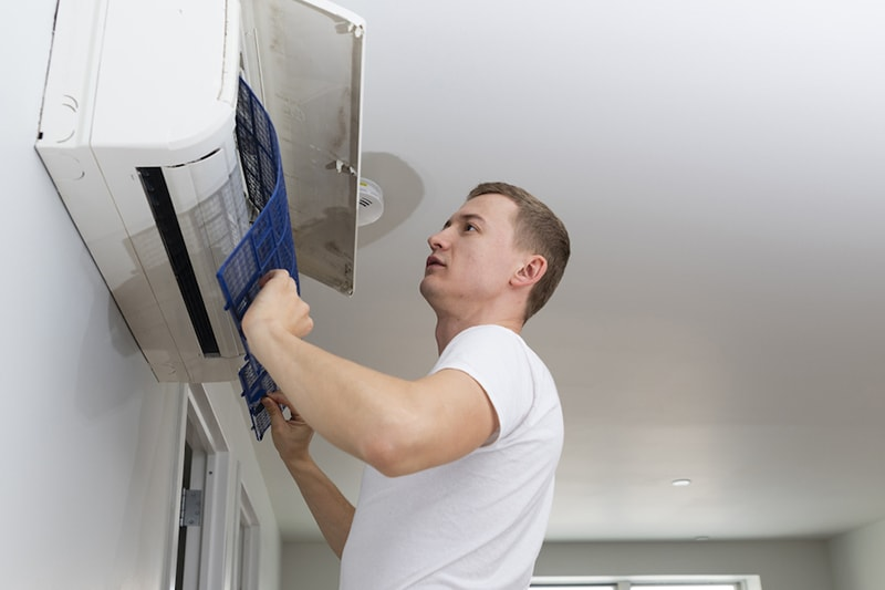 Young man cleaning filters in the air-conditioning split device, The Problem With Clogged Air Filters | Indoor Air Quality | Weaverville, NC