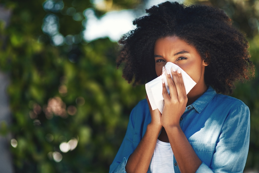 Portrait of a young woman blowing her nose with a tissue outside.