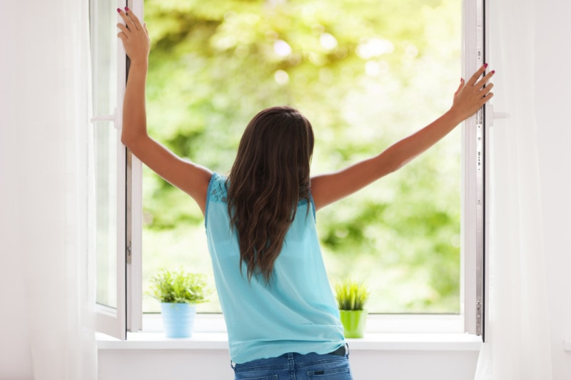Young girl standing in front of an open window in summer.